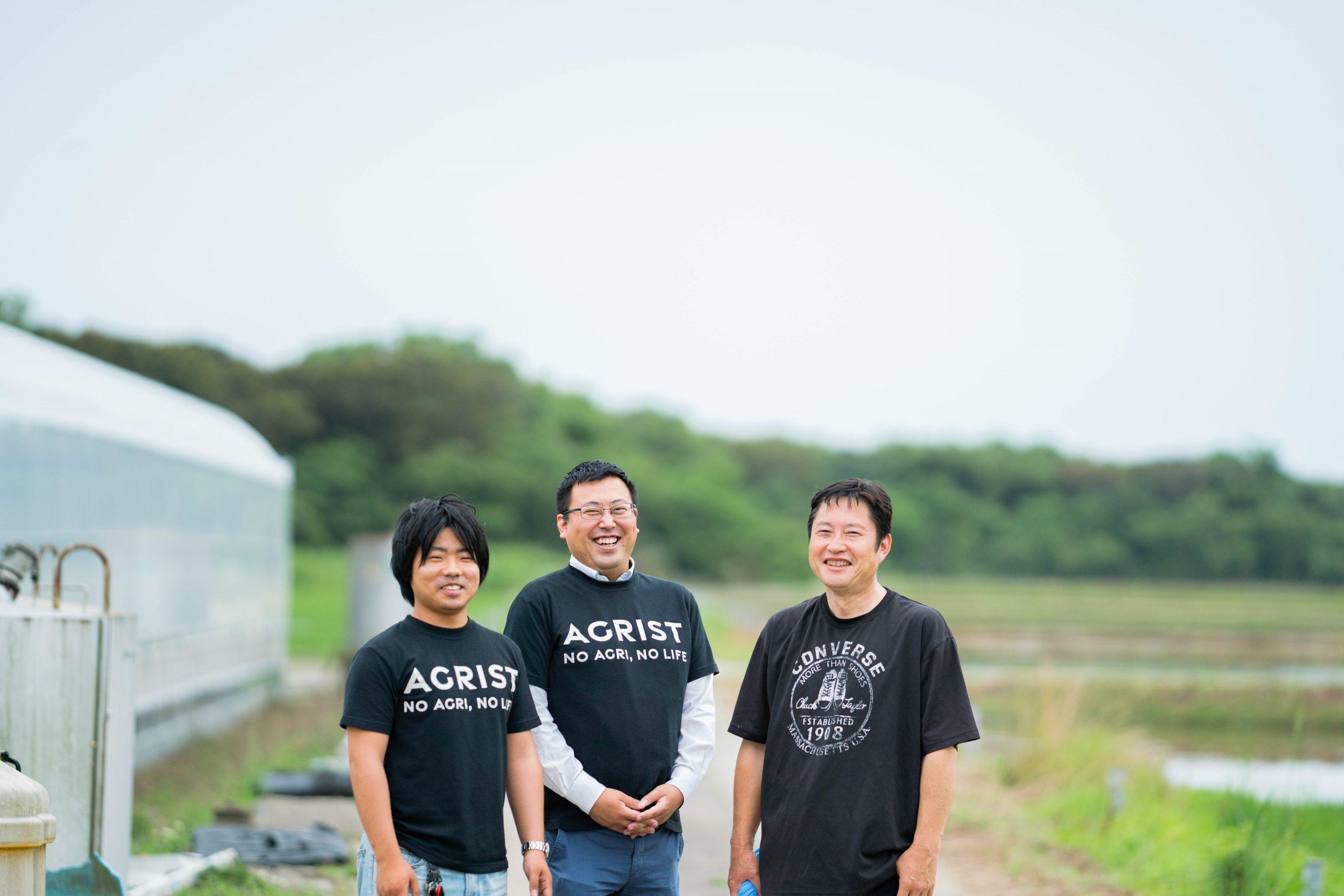 農家の福山さん(中央)とビニールハウス外